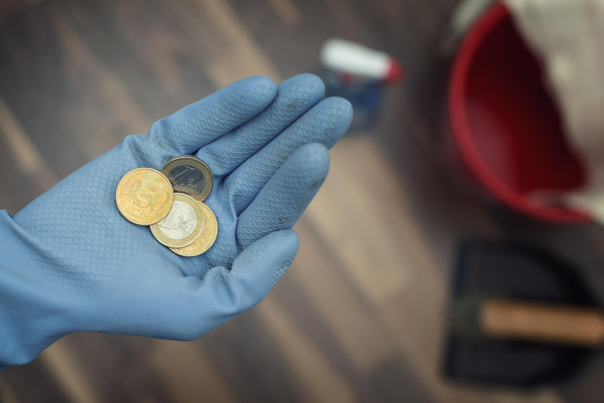 Siivooja pitää kolikoita sinisellä siivoushansikkaalla verhotussa kädessään.
