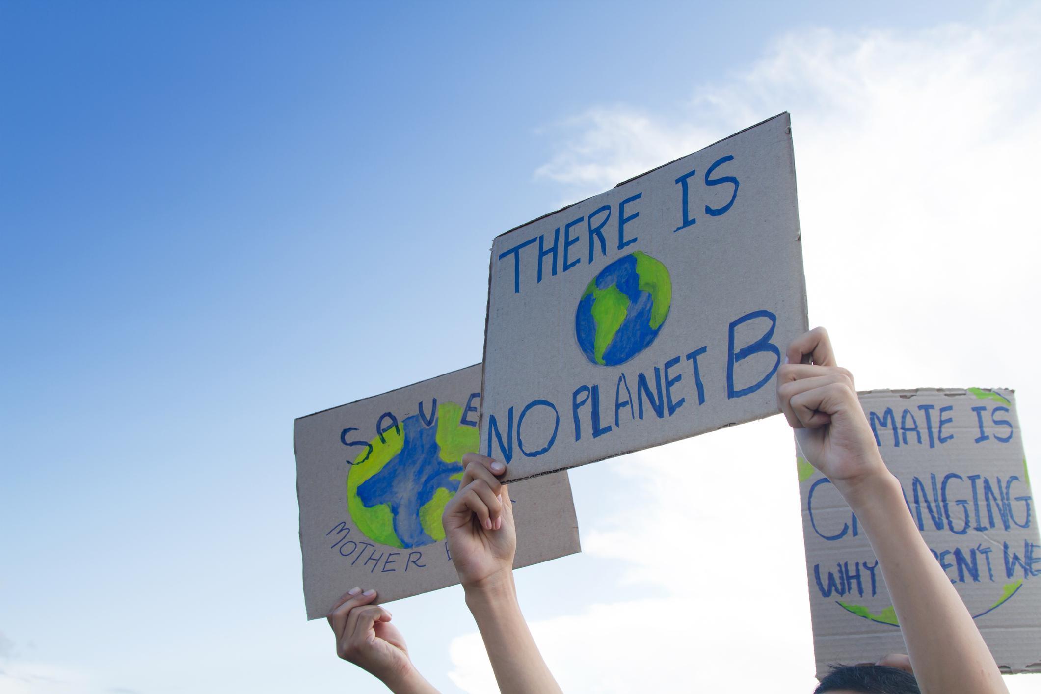 Ihmisiä mielenosoituksessa näyttämässä pahvinpaloilta iskulauseita, joissa kannatetaan ilmastonmuutoksen torjumista.