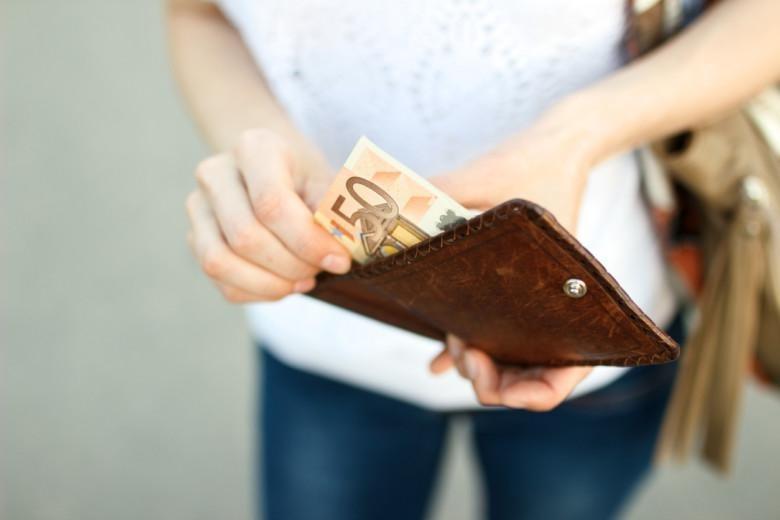 Nainen ottaa lompakosta 50 euron seteleitä.