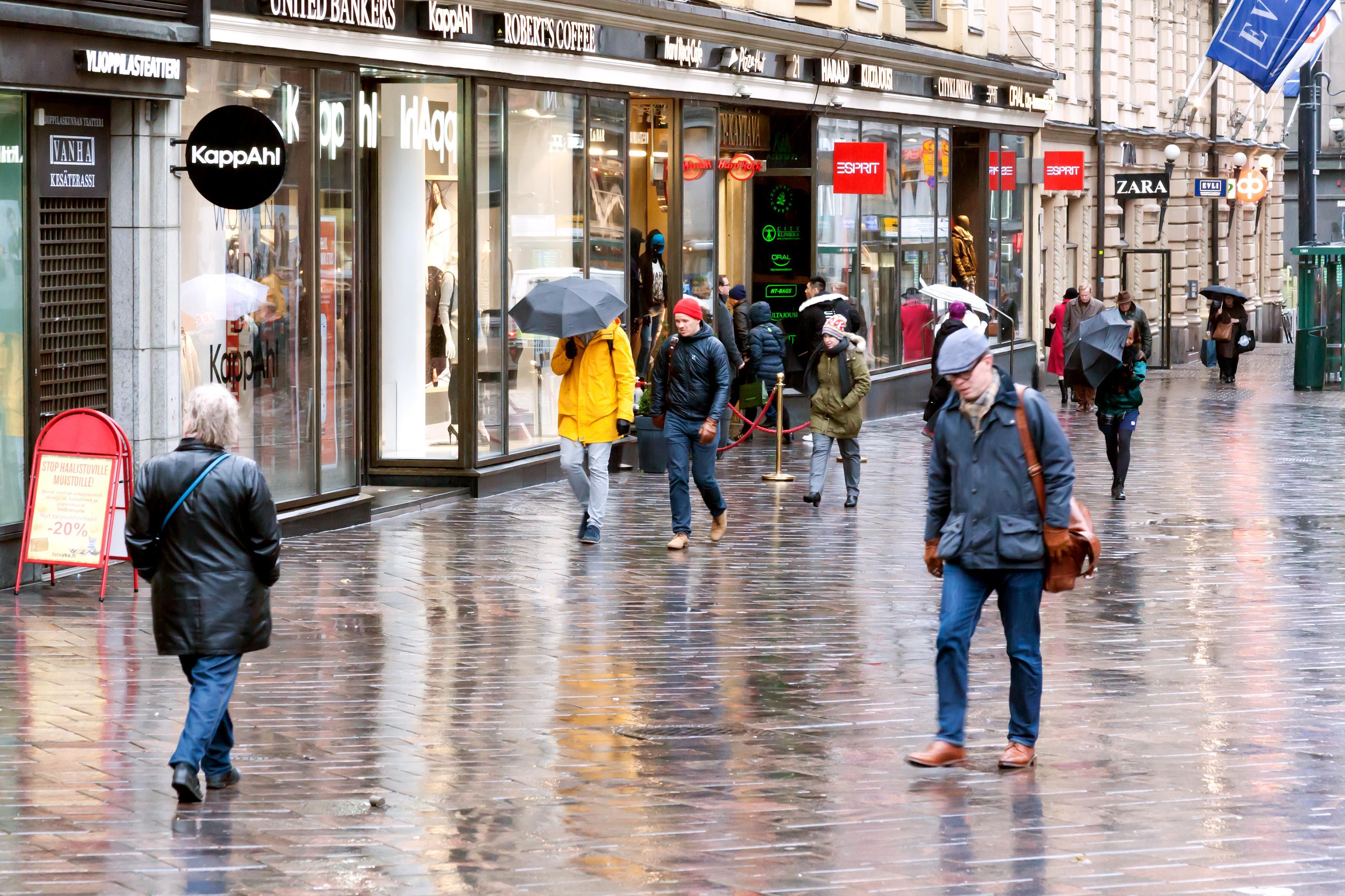 Ihmisiä kävelemässä lokakuisessa sateessa helsinkiläisellä kadulla. Kuva: iStock.com / Aleksei Andreev