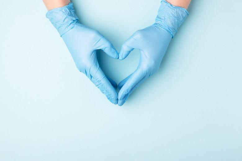 Kädet sinisissä terveydenhoitoalan hansikkaissa asetettu sydämen muotoon.