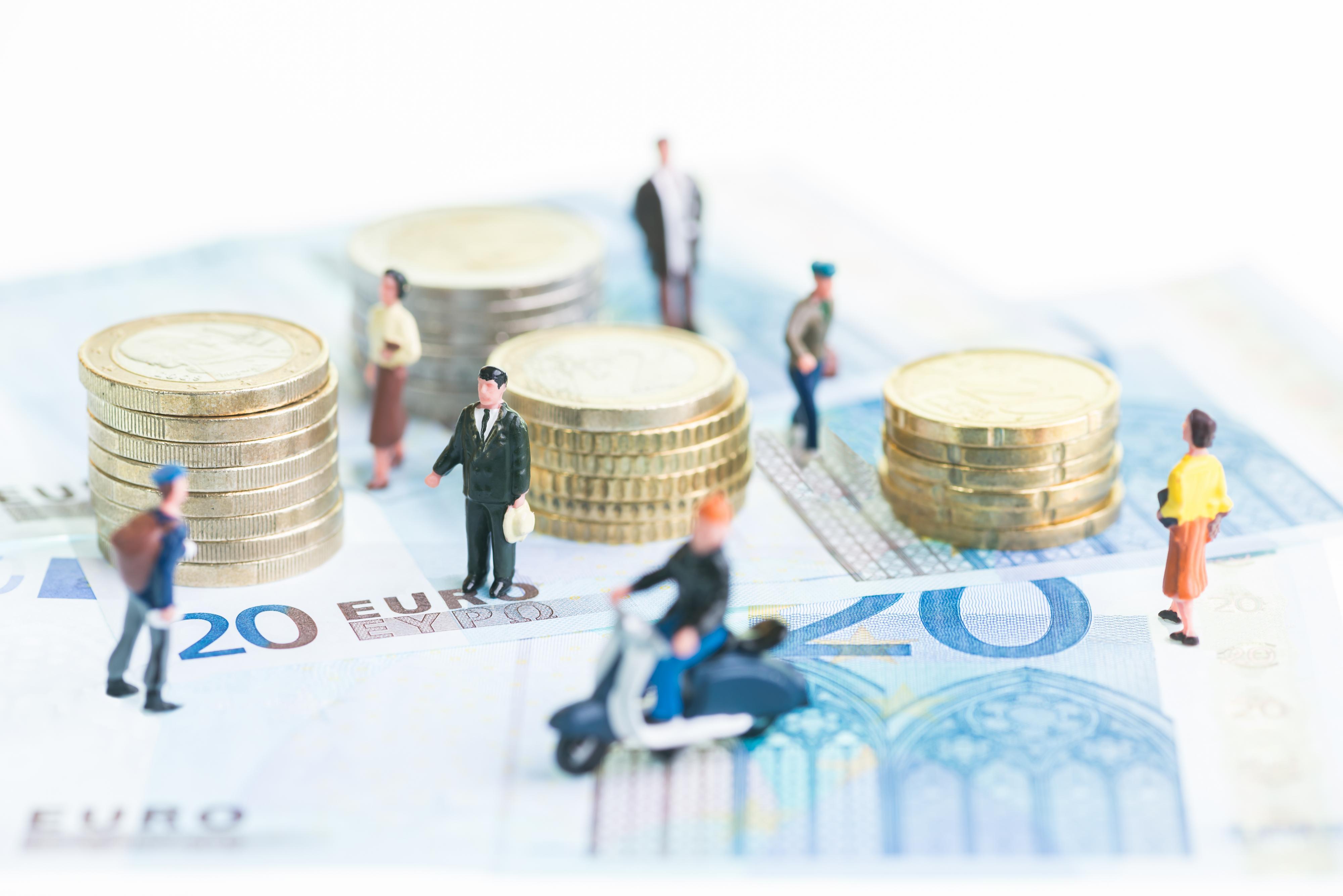 Minikokoisia ihmishahmoja euroseteleiden ja -kolikoiden keskellä