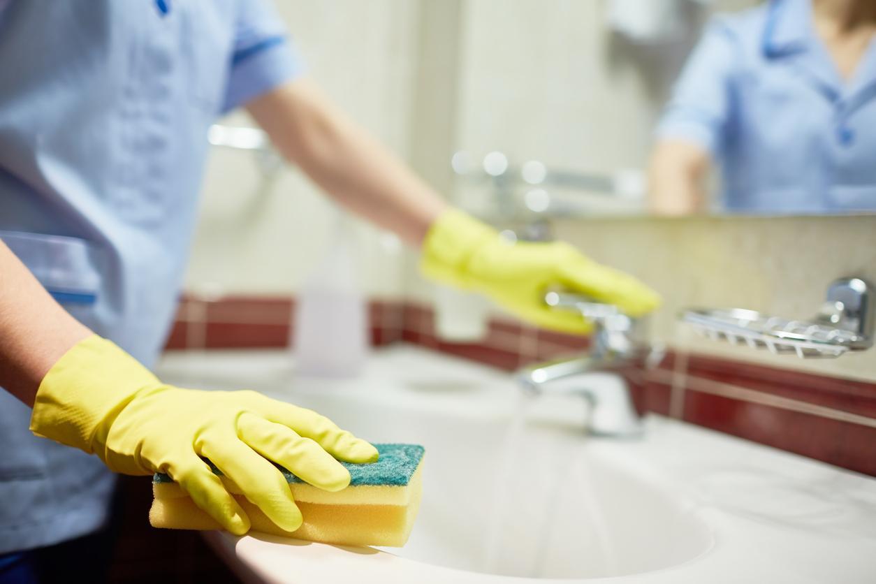 Siivooja siivoamassa kylpyhuonetta pesusienellä.