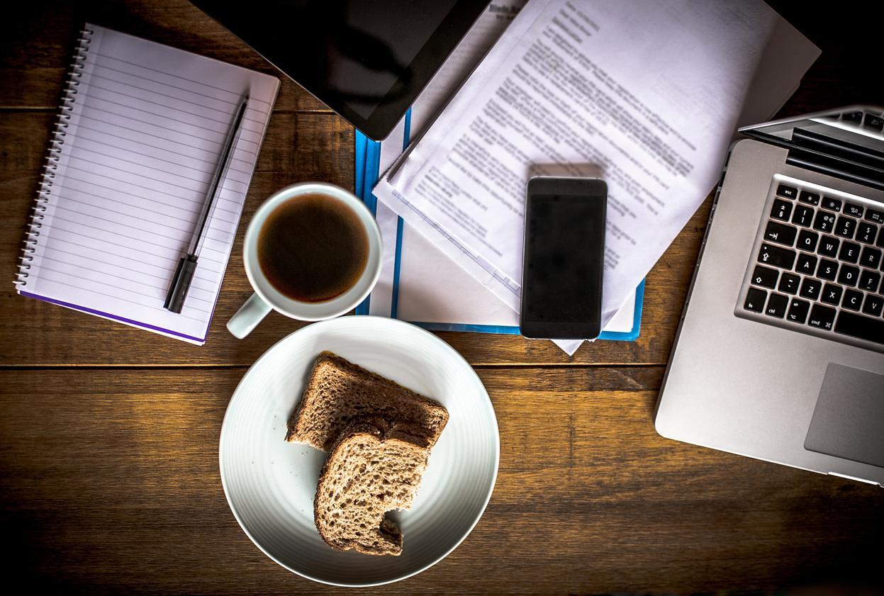 Kannettava tietokone, kahvikuppi ja välipala kotona työpöydällä.