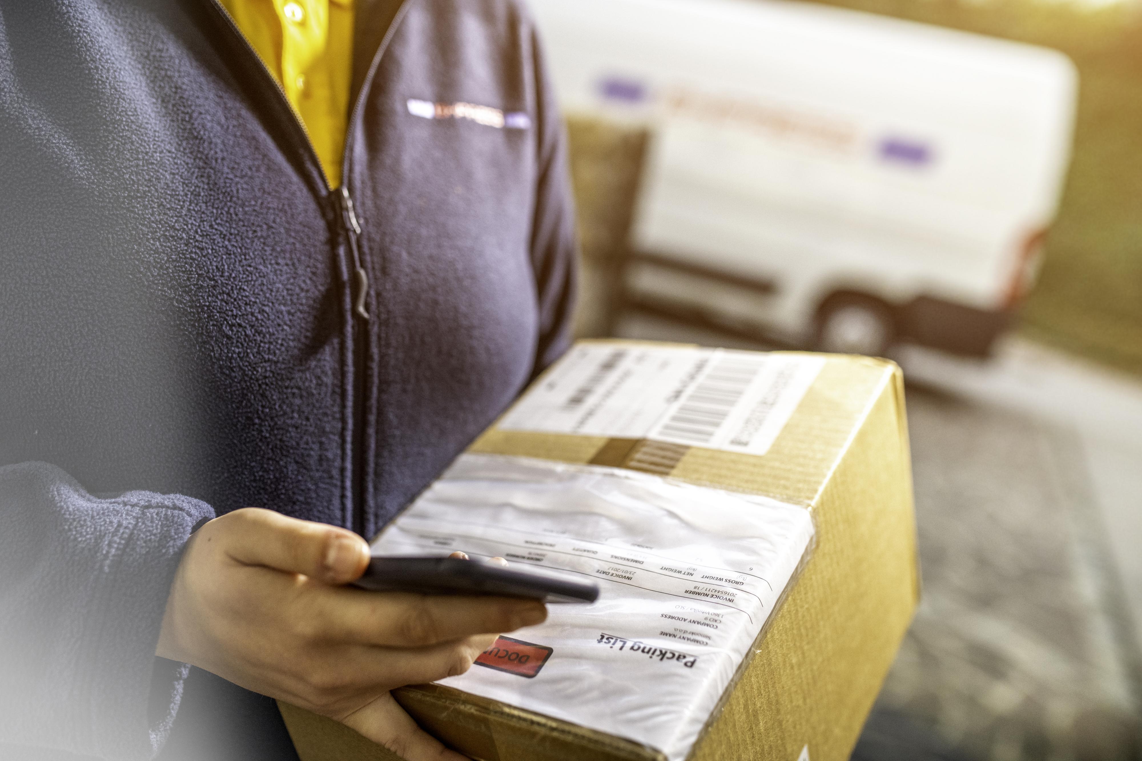 Naispuolinen tavarantoimittaja kuittauttamassa lähetystä älypuhelimella.