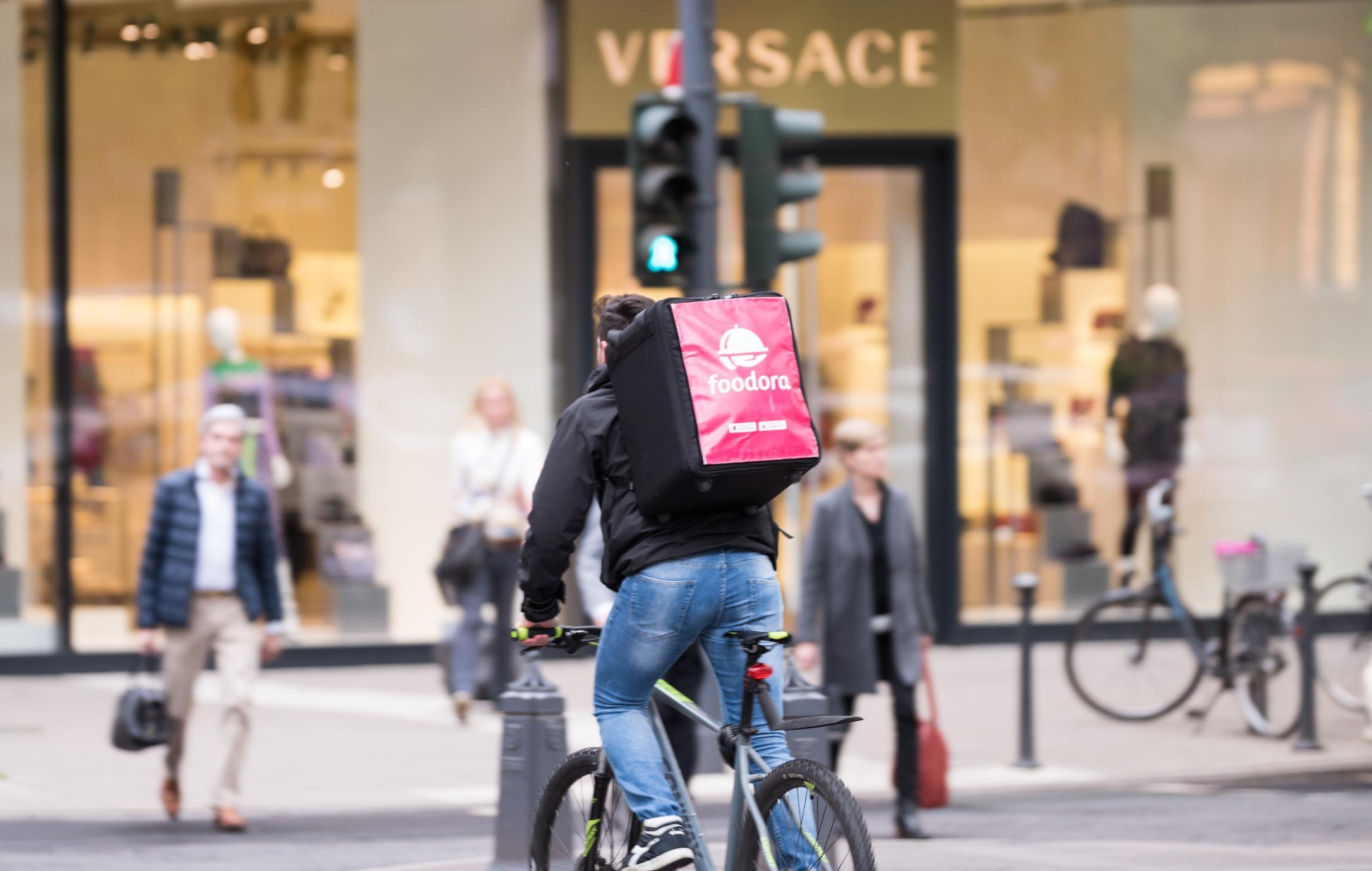 Foodora-pyörälähetti ylittää Königsalleen Düsseldorfissa, Saksassa.